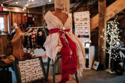burlap shawl with red sash positioned on a mannequin.