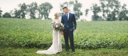 bride and groom in front of soy bean field
